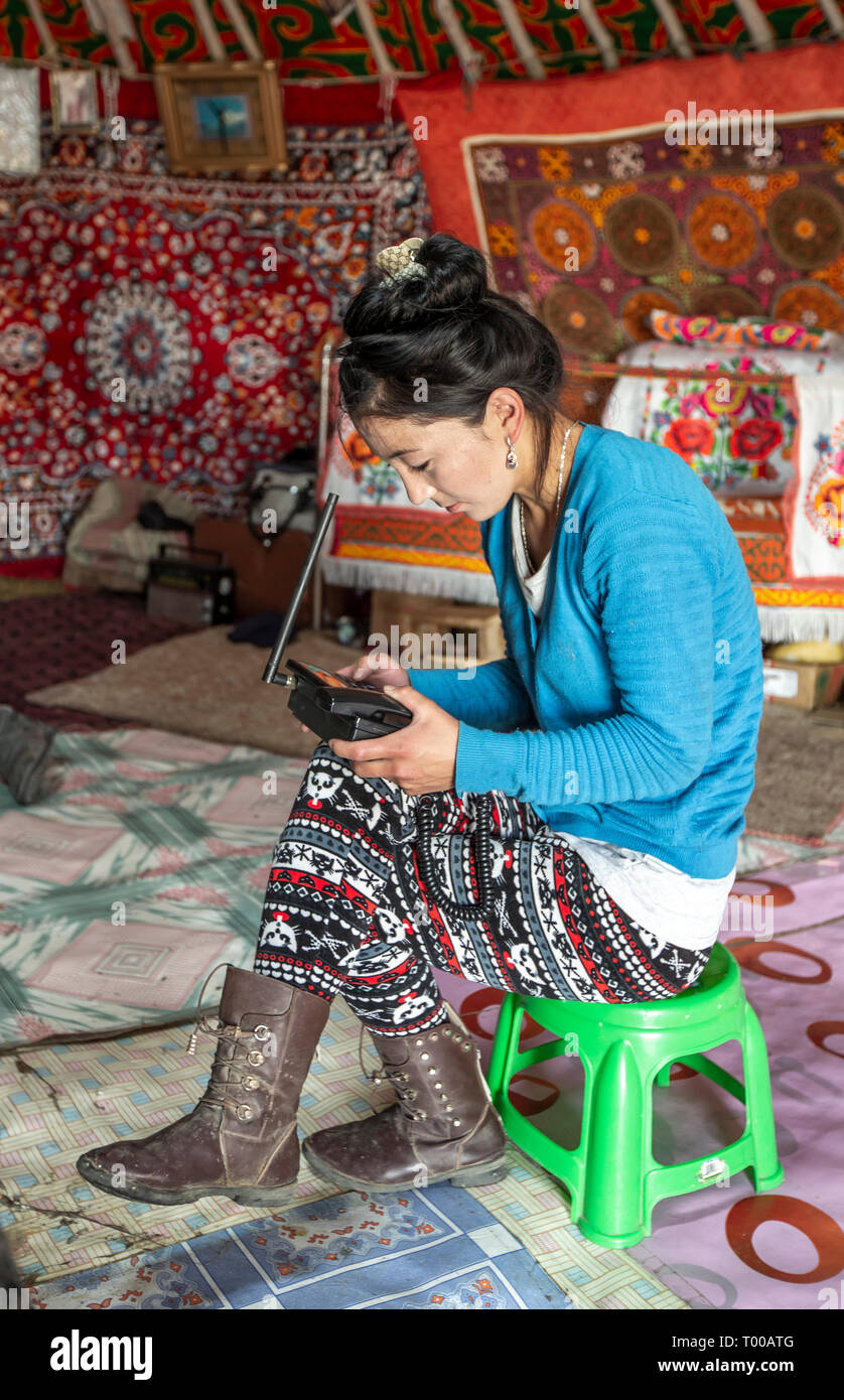 Bayan Olgii, Mongolia, 29th September 2015: Mongoilian kazakh nomad  woman waiting for a phone call  in her home yurt Stock Photo
