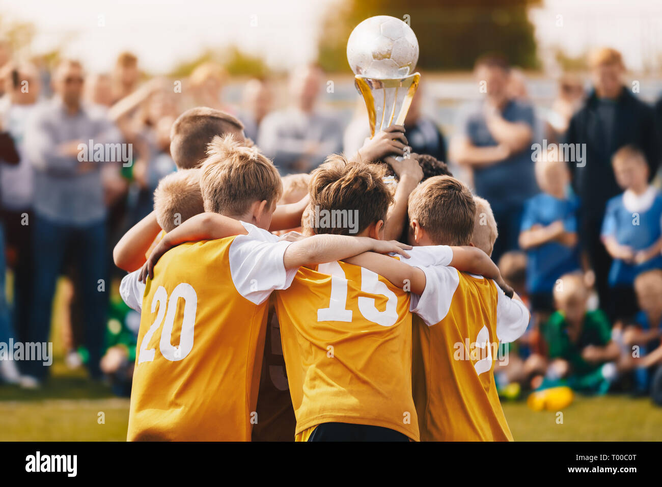Kids Holding Golden Cup. Boys Winning Soccer Championship. Children Raising Trophy to the Sky in Sunny Summer Day. Football Champion Team Stock Photo