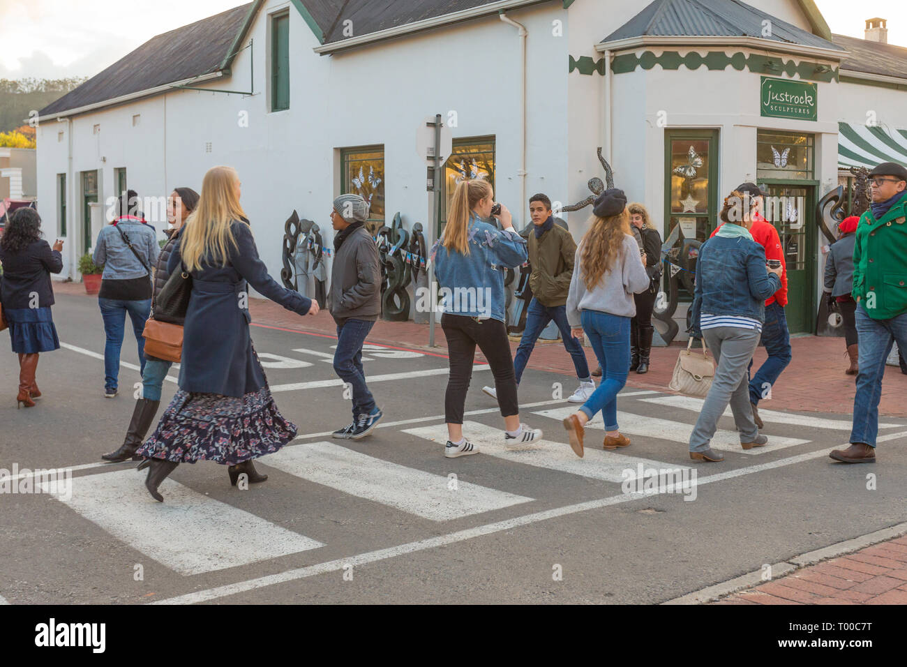 pedestrians or people crossing the road at a zebra crossing in Franschhoek village on a cold Winter day Cape Winelands, South Africa Stock Photo