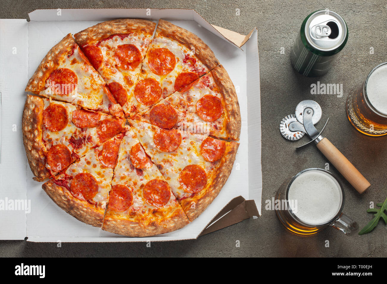 Italian fast food. Delicious hot pepperoni pizza in a box, and glass of beer sliced and served on brown table, close up view. Concept of fast food and Stock Photo