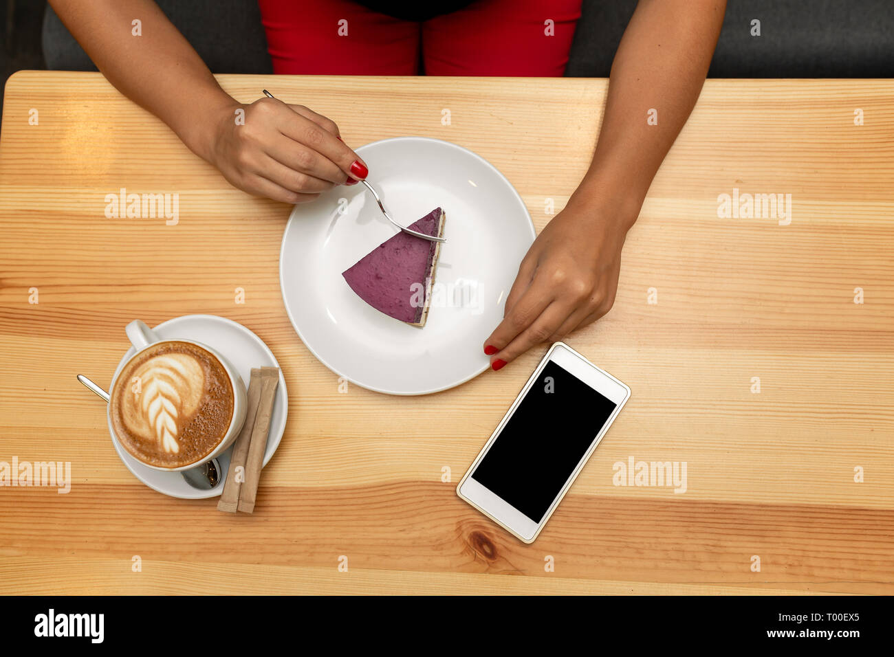 View from above on woman hands on wooden table hold coffe cup near cheesecake and smartphone. Stock Photo