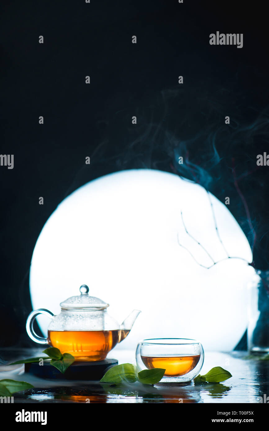 Asian tea ceremony with a full moon. Glass tea bowl and teapot against a shining circle. High contrast drink photo - Stock Image