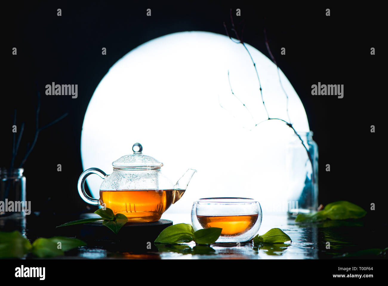 Tea in a double wall bowl and teapot against the full Moon. Chinese tea ceremony concept with copy space - Stock Image