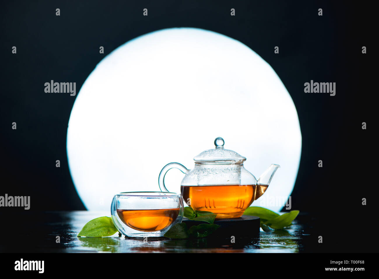 Asian tea ceremony still life header with a full moon. Glass tea bowl and teapot against a shining circle. - Stock Image