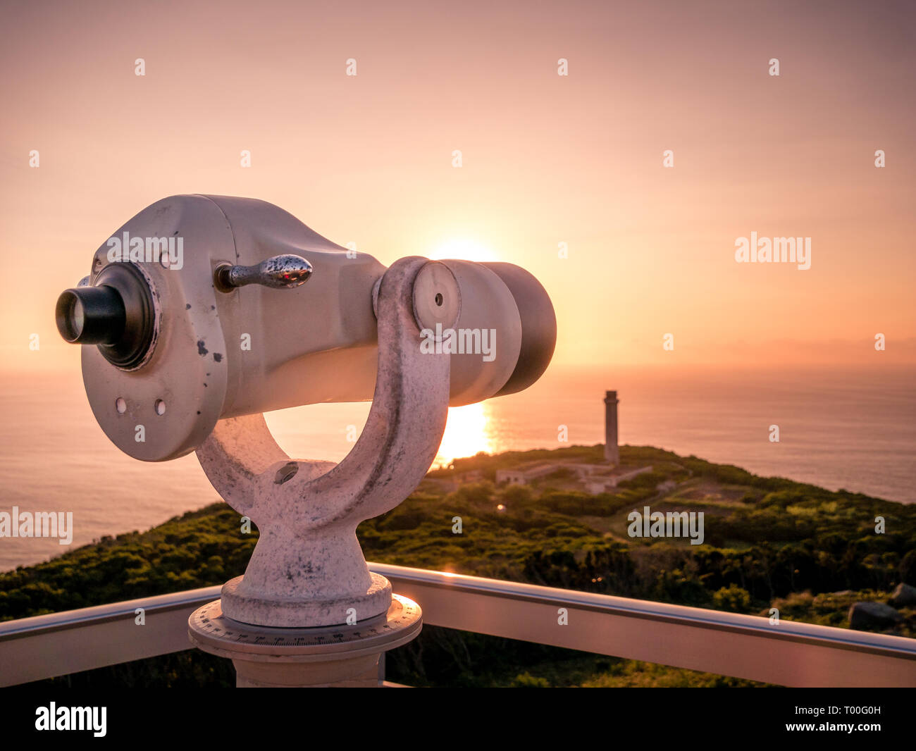Image of viewpoint with binoculars during colorful sunset pointing at the ocean on the Azores, Portugal, Europe - Stock Image
