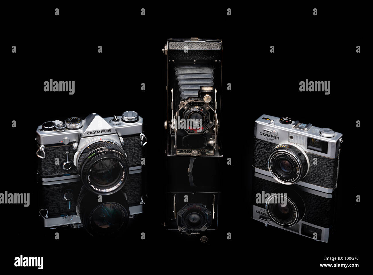 Collection of classic vintage  film cameras including Olympus OM1 35 mm  Single Lens Reflex SLR, Kodak 6-20 folding camera and Olympus RC rangefinder - Stock Image