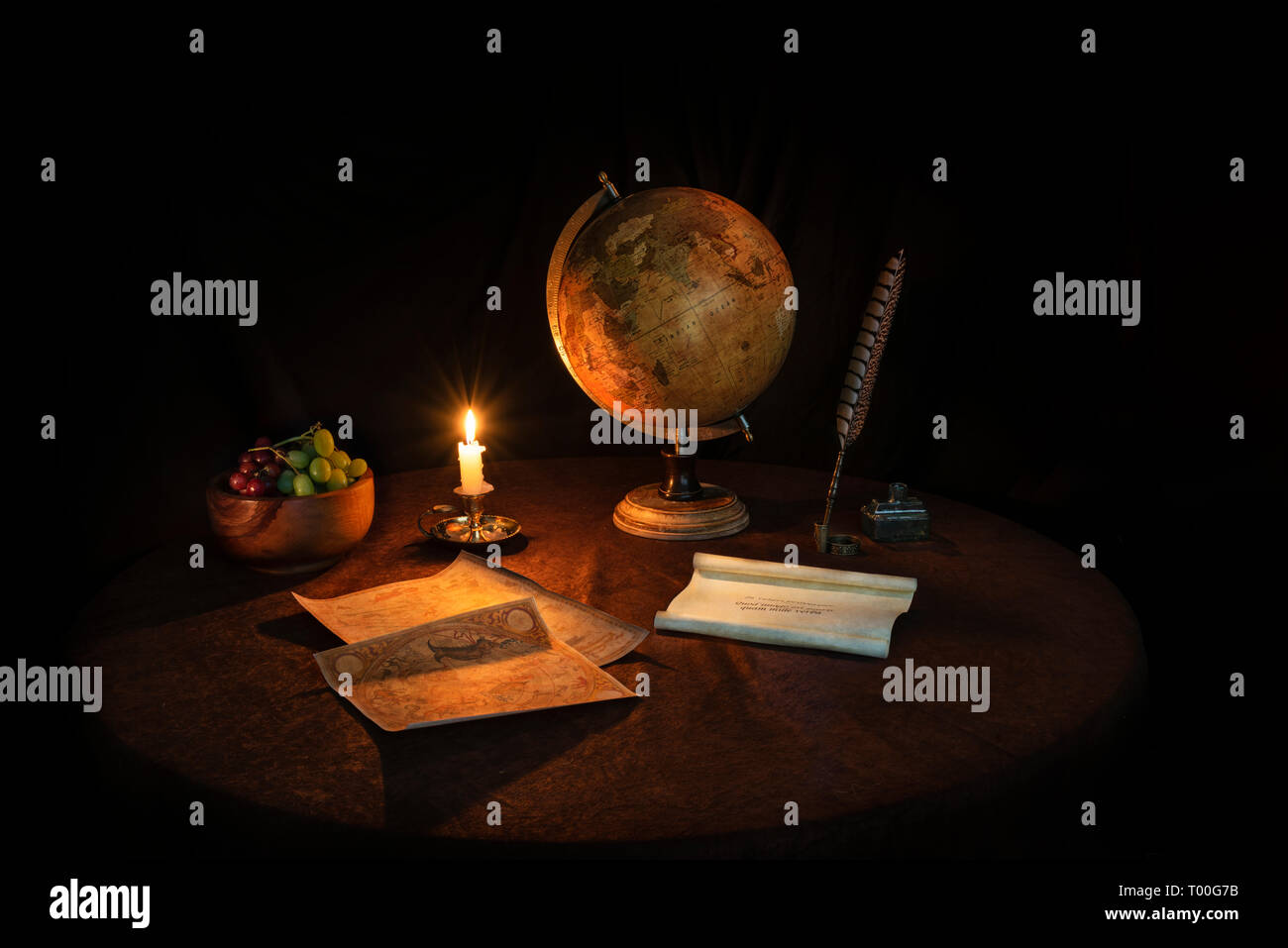 Still Life by candlelight with globe quill pen vellum scroll and fruit bowl - Stock Image