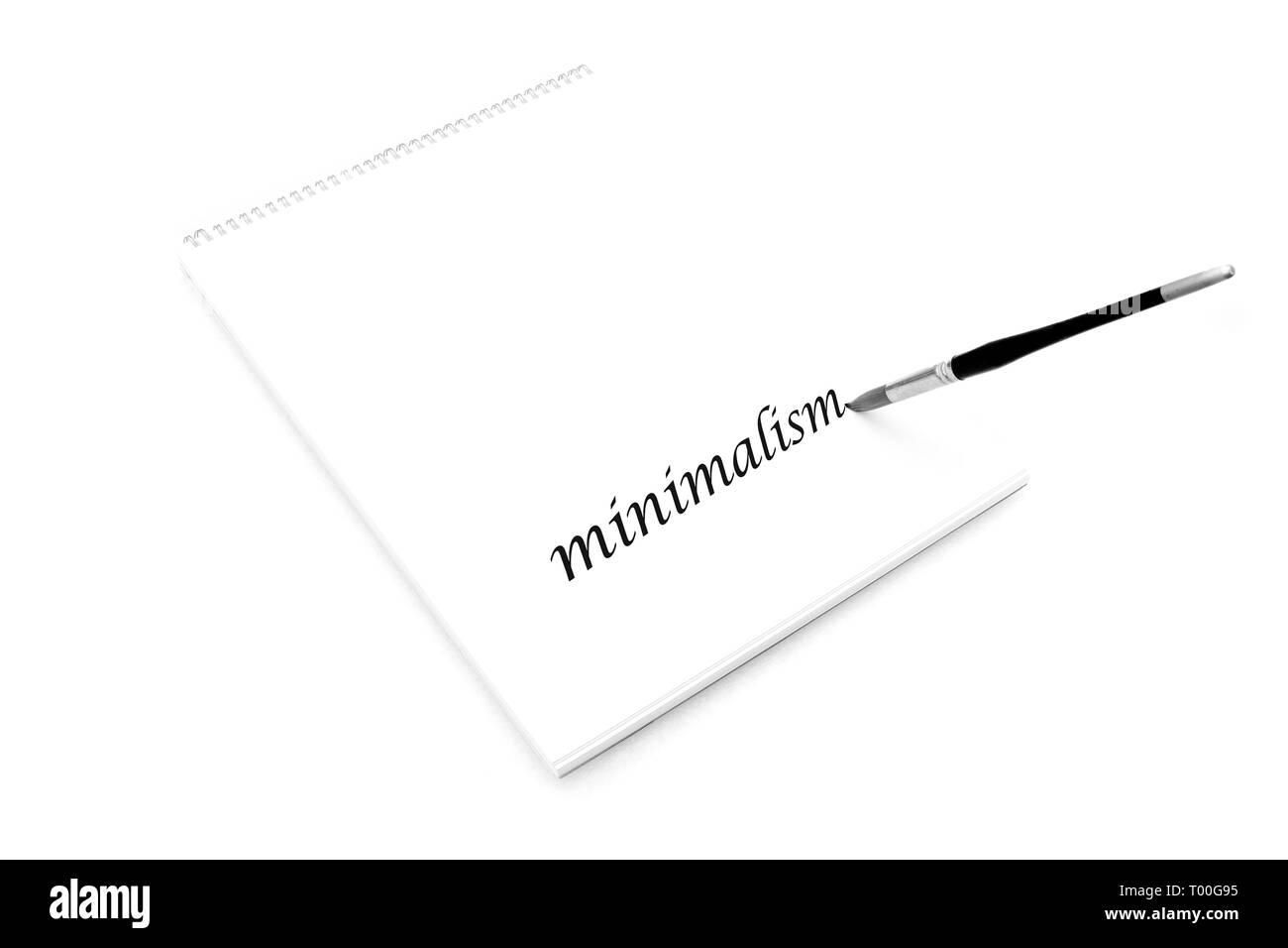 Minimalism, minimalist concept white paper notepad with paintbrush writing - Stock Image