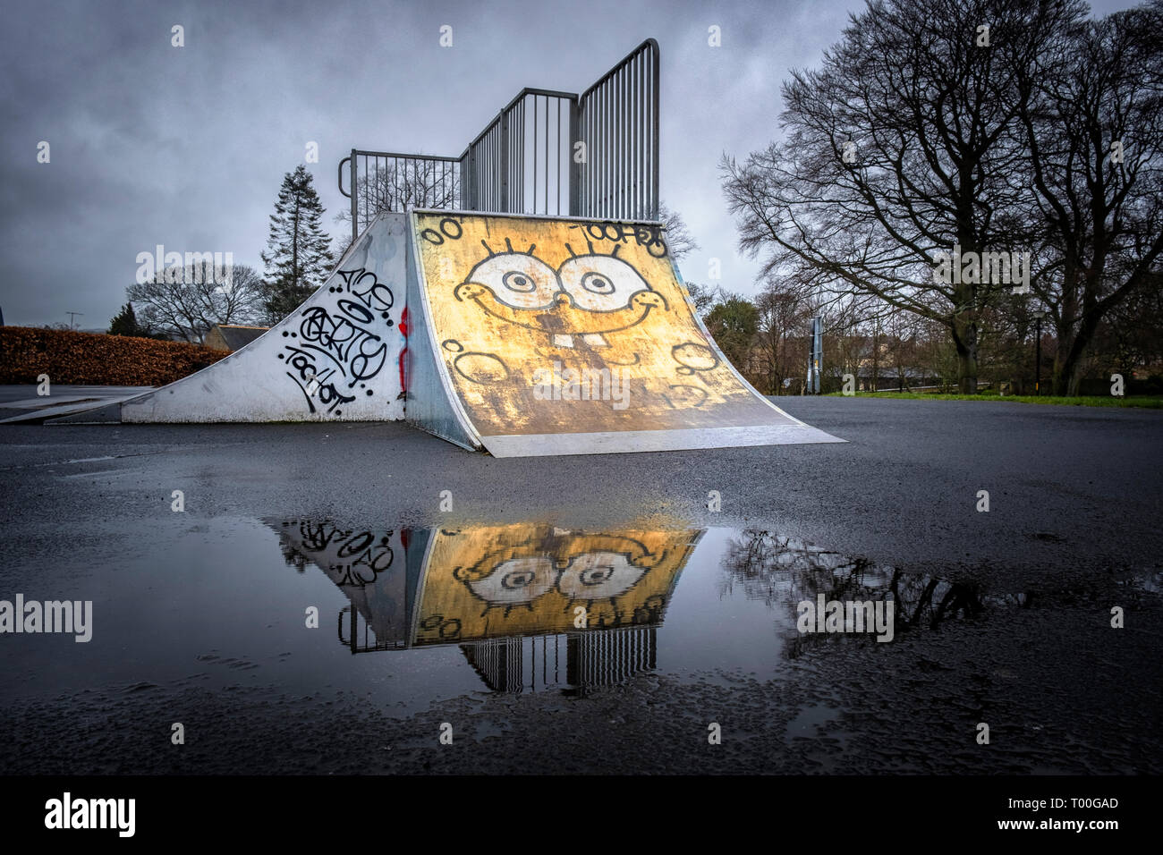 Empty children's playground with graffiti face painted on an deserted skateboard ramp reflected in puddle in dismal wet weather - Stock Image