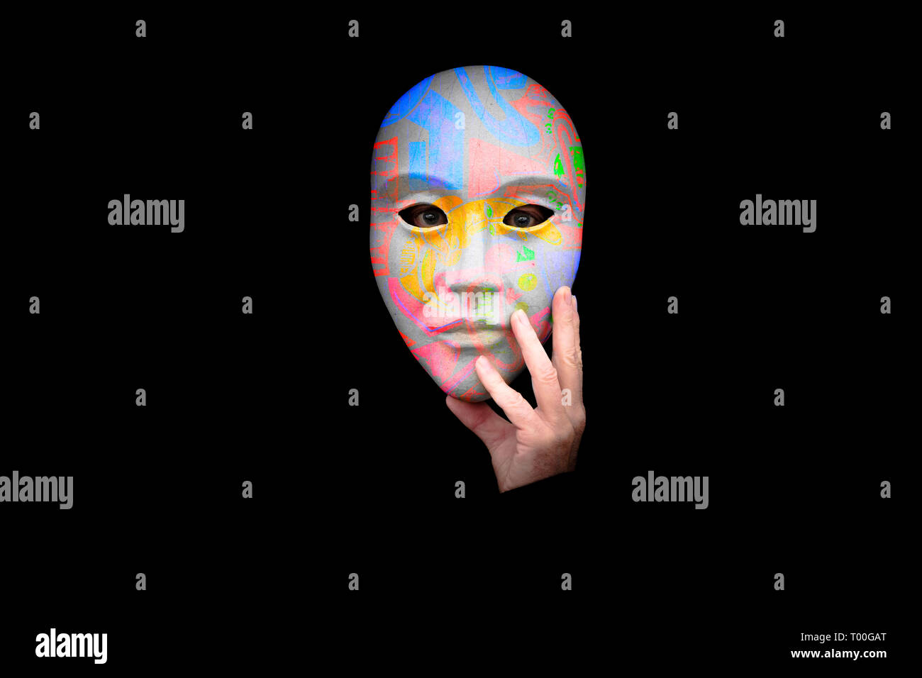 Person with hand to face  in a colourful mask against a black background - Stock Image