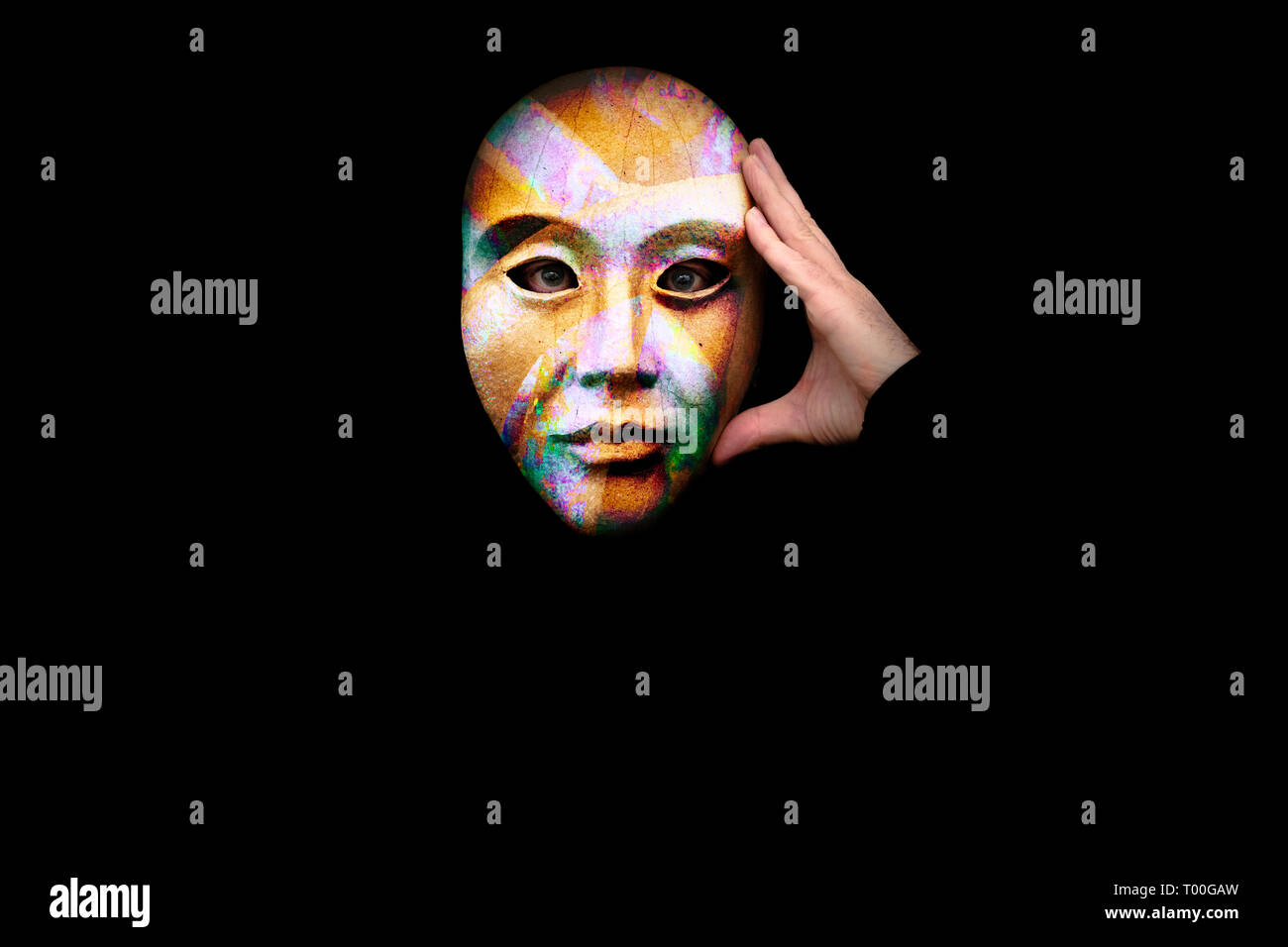 Perplexed person with hand to head wearing a colourful mask against a black background - Stock Image