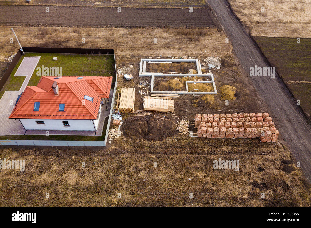 Aerial view of new house roof with attic windows and building site, foundation of future house, stacks of bricks and building timber logs for construc Stock Photo