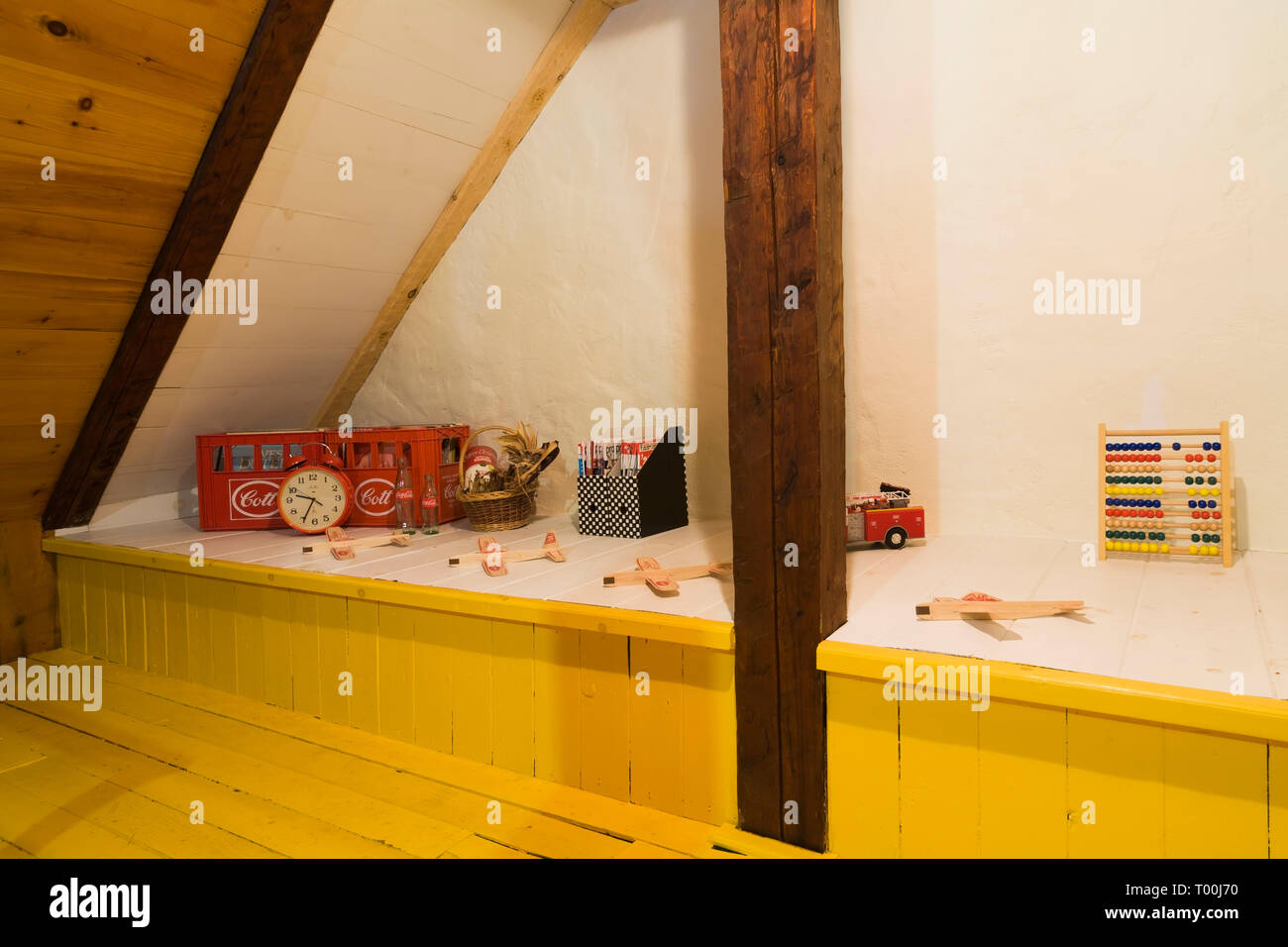 Vintage collectibles on raised platform in attic room with yellow painted pinewood floorboards inside an old circa 1760 Canadiana fieldstone home - Stock Image