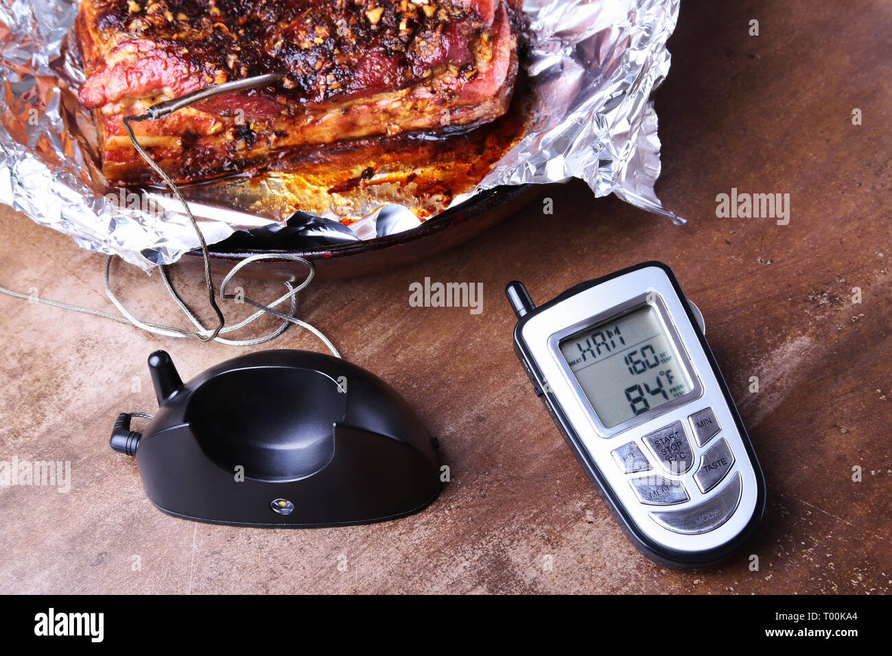 Grilled Steak in a pan and Wireless Remote Digital Cooking Food Probe Meat Thermometer For Grill on a black background. Copy space. - Stock Image