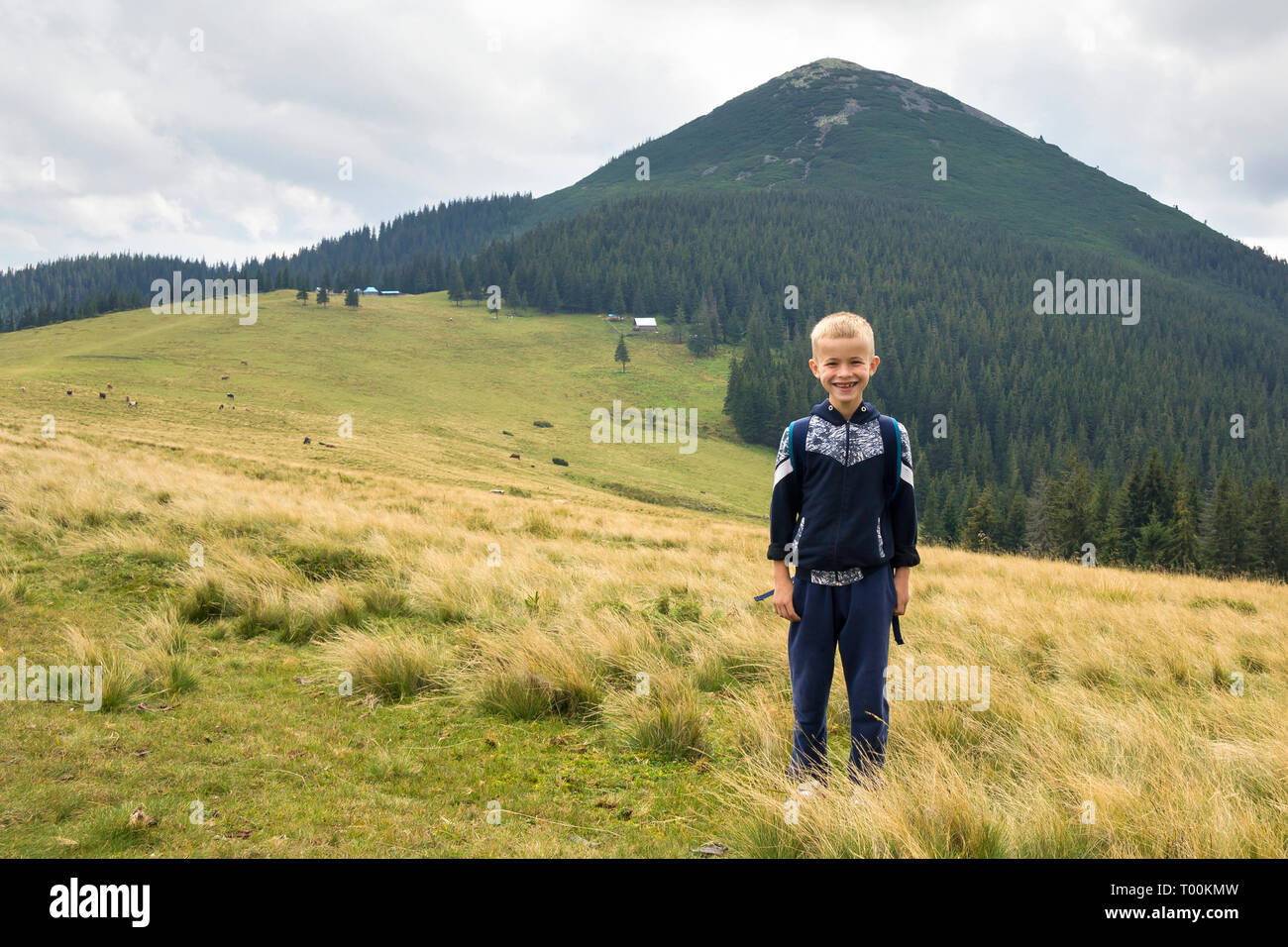 Young happy smiling child boy with backpack standing in mountain grassy valley on background of summer landscape, woody mountain view. Active lifestyl - Stock Image