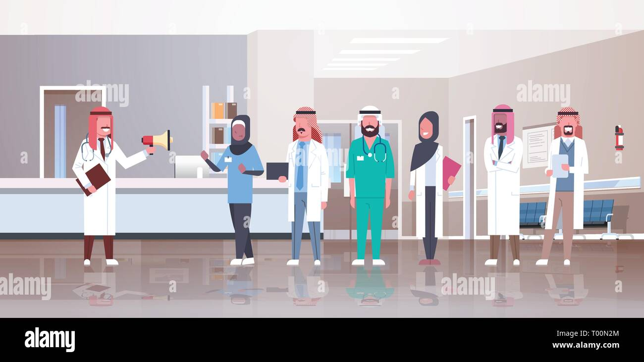 arab male doctor holding loudspeaker shouting through megaphone arabic doctors team meeting conference hospital medicine workers group clinic corridor - Stock Image