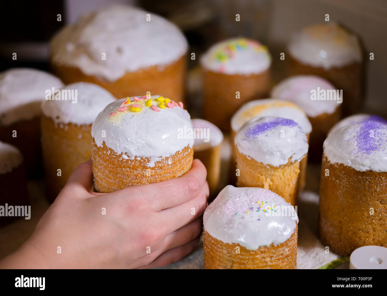 Baker decorates the upper part of Easter cakes covered with white sugar icing by colored granulated sugar pouring decoration on fresh icing making tra - Stock Image