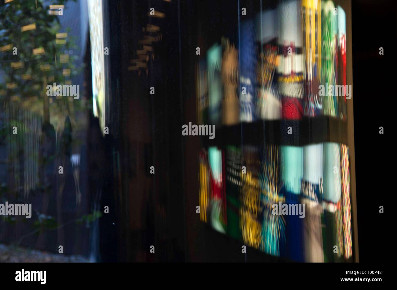 A curved window reflects an art exhibit at the De Young Museum in San Francisco, CA. - Stock Image