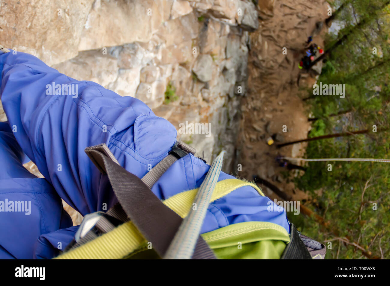 Climber's legs hanging on a rope in a harness, first person view from top to bottom - Stock Image