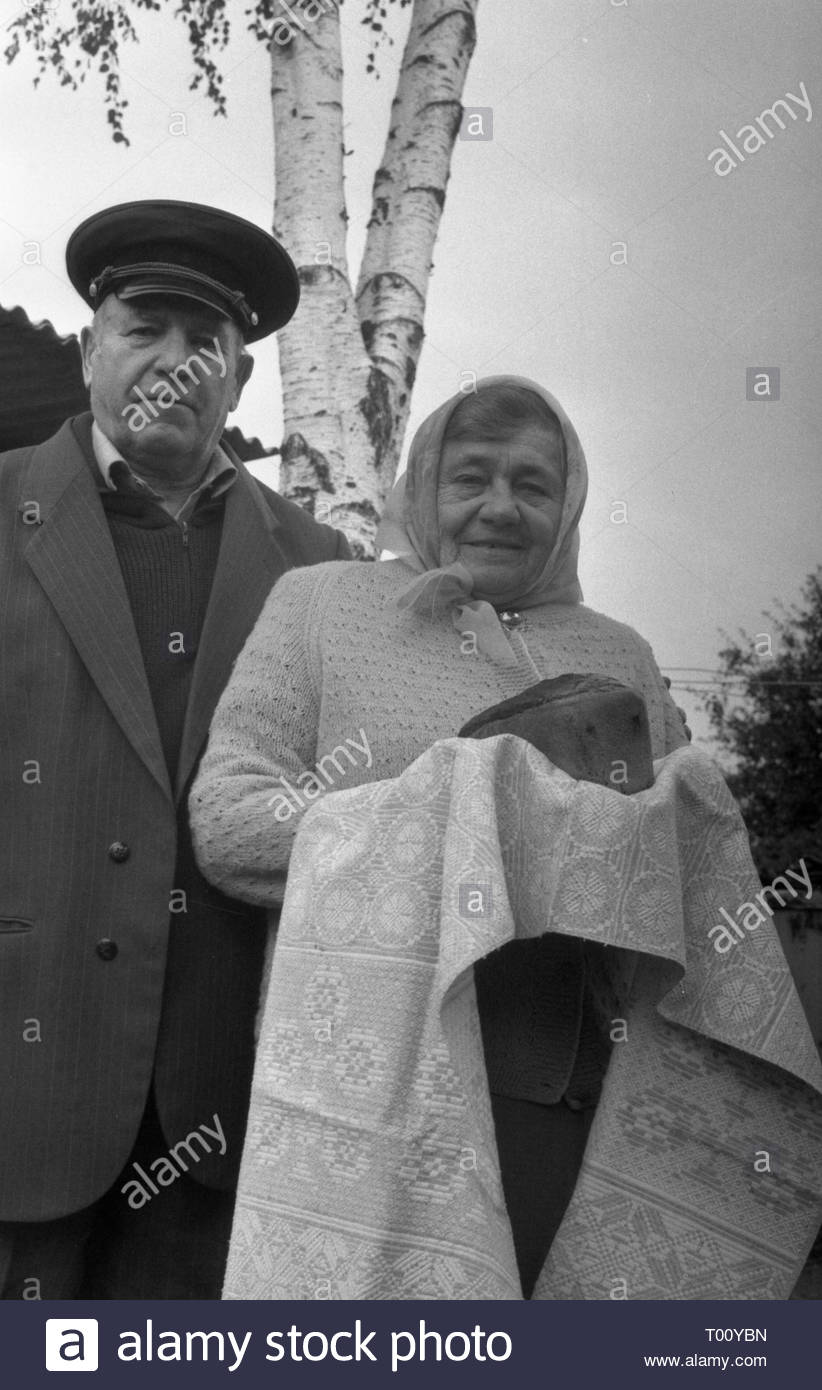 The photo shows the portrait of an elderly couple who lived together for many years. Woman is holding towel with bread. According to the Slavic tradition so we meet our guests. We are always welcome guests! Welcome to Belarus! - Stock Image