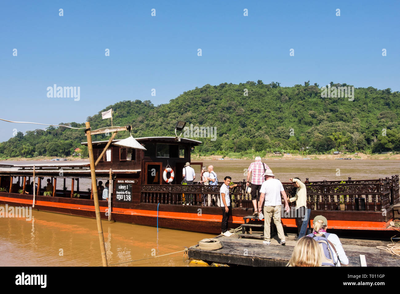 Tourists boarding a traditional wooden boat for a cruise up the Mekong River from Luang Prabang, Laos, southeast Asia Stock Photo