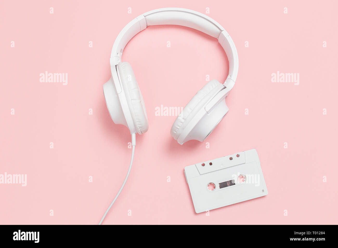 White cassette tape and headphones on a pink background. Party 90s concept. - Stock Image