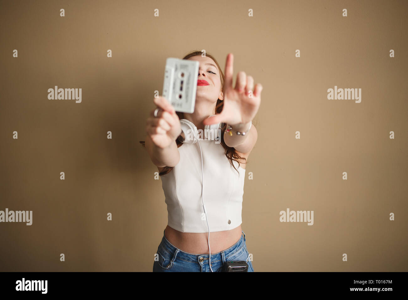 Young hipster woman with white retro audio cassette. Party 90s concept. - Stock Image