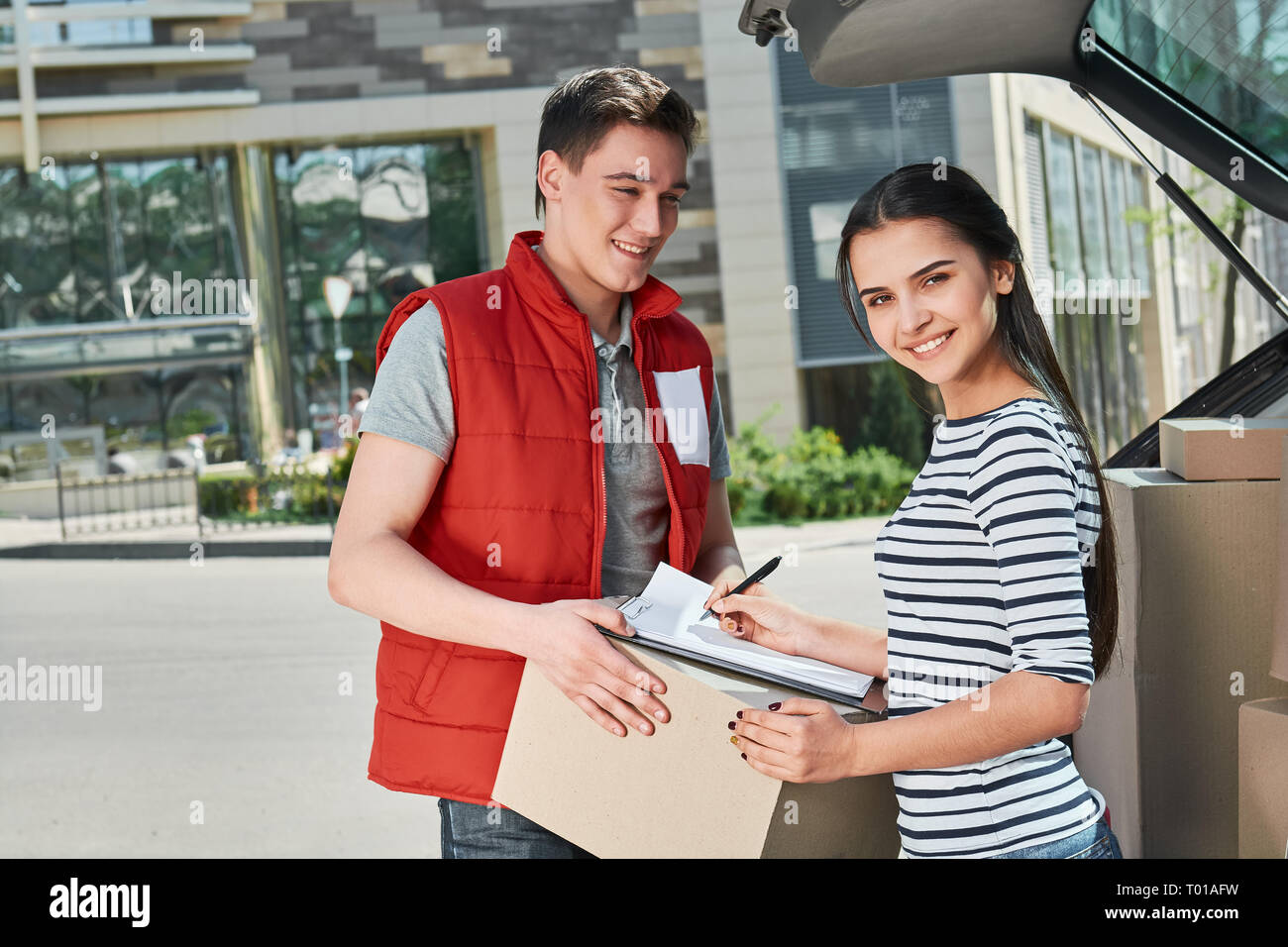 Cheerful man wearing red postal uniform is delivering parcel to a satisfied client. He brought her a parcel directly to the trunk of her car. Dark-haired woman is signing receipt of delivery package. Friendly worker, high quality delivery service. Outdoors. - Stock Image