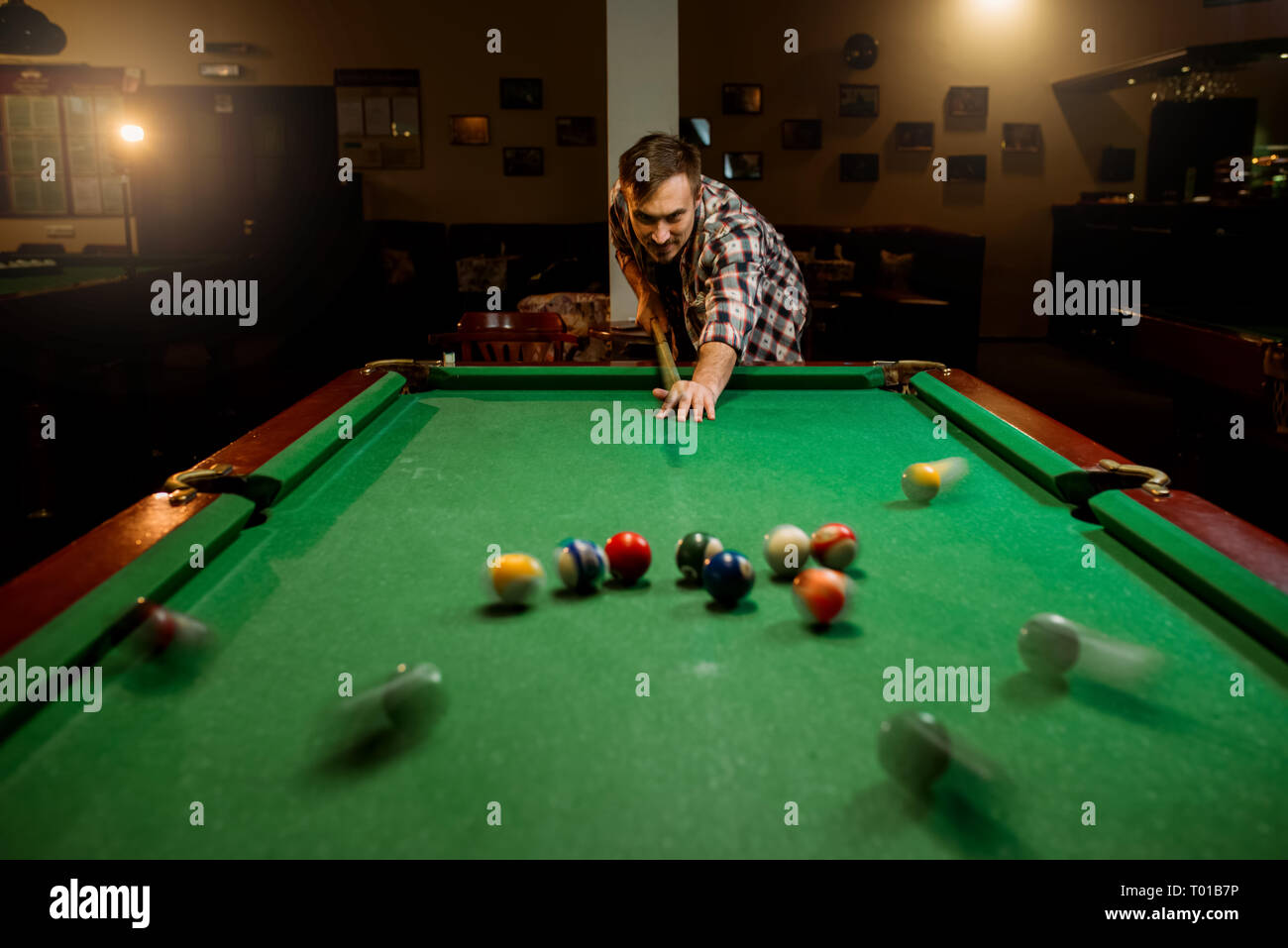 Male billiard player with cue at the table - Stock Image