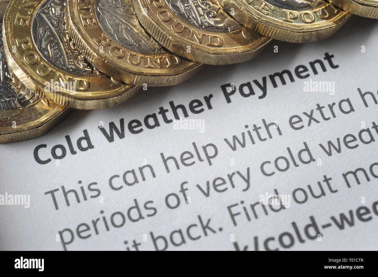 DWP COLD WEATHER PAYMENT LEAFLET WITH ONE POUND COINS RE BENEFITS THE ELDERLY PENSIONERS LOW INCOME PENSION CREDIT ETC UK - Stock Image