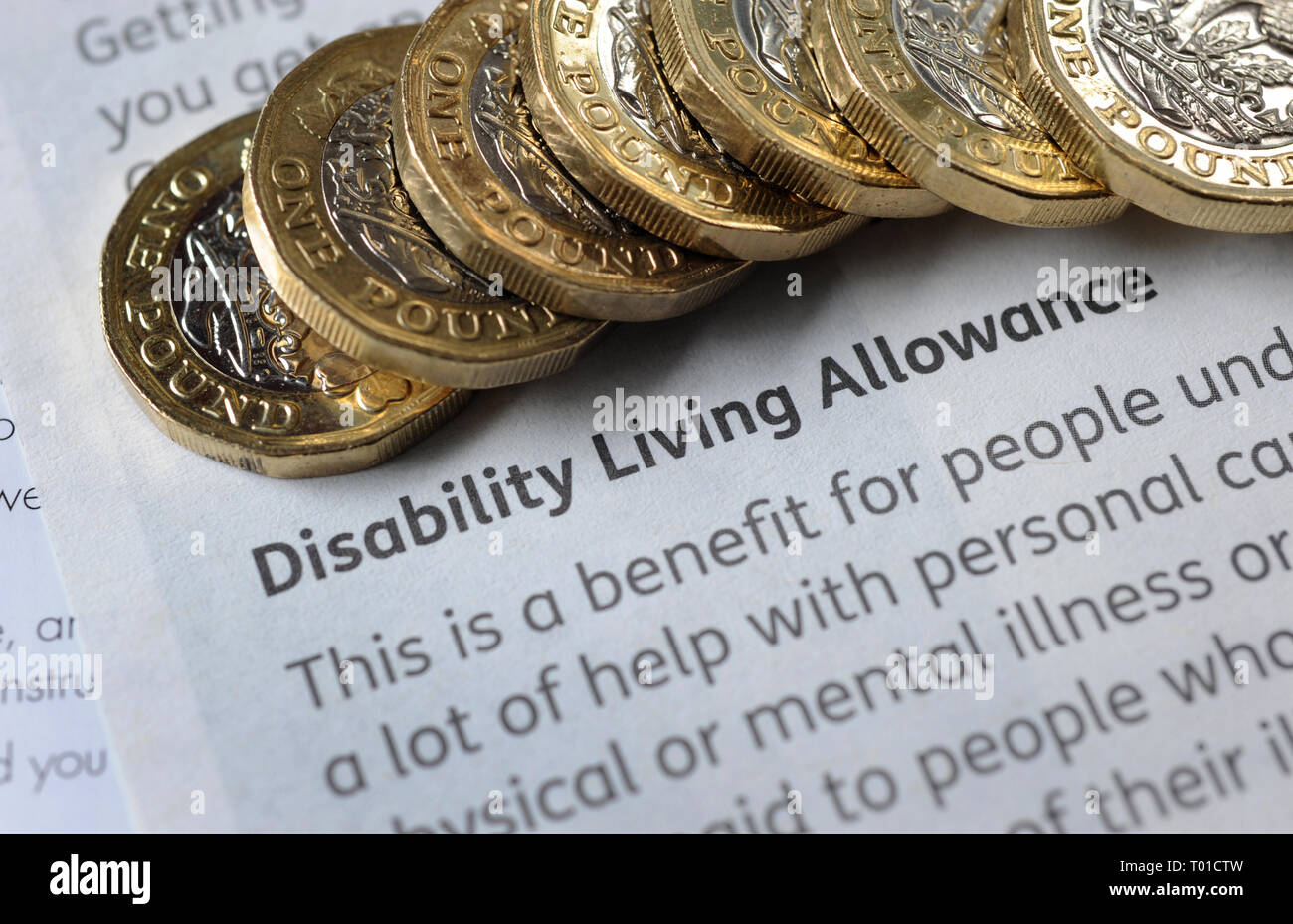 DWP  DISABILITY LIVING ALLOWANCE LEAFLET WITH ONE POUND COINS RE BENEFITS THE ELDERLY PENSIONERS LOW INCOME PENSION CREDIT ETC UK - Stock Image