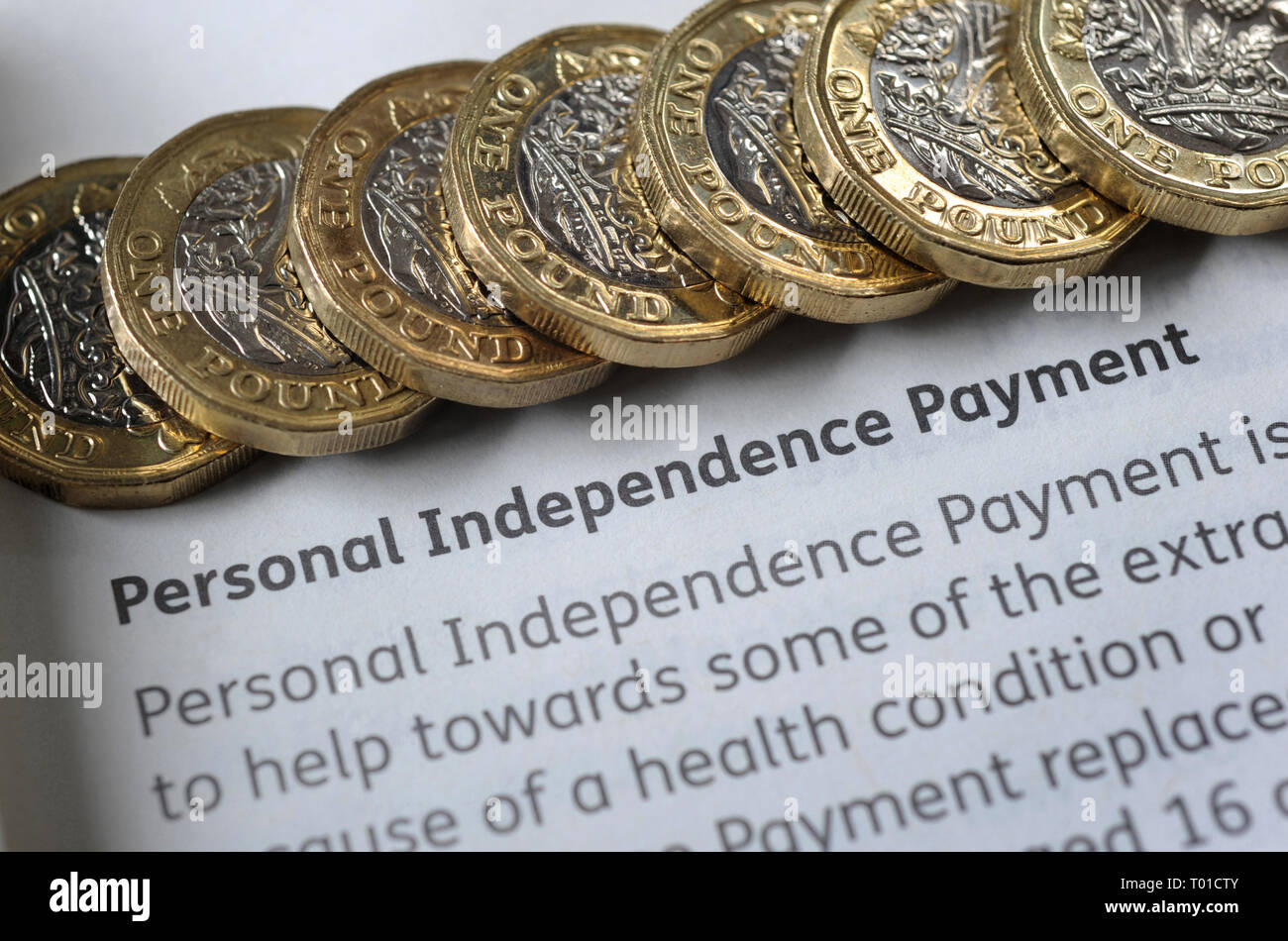 DWP PERSONAL INDEPENDENCE PAYMENT LEAFLET WITH ONE POUND COINS RE BENEFITS THE ELDERLY PENSIONERS LOW INCOME DISABILITY PENSION CREDIT ETC UK - Stock Image