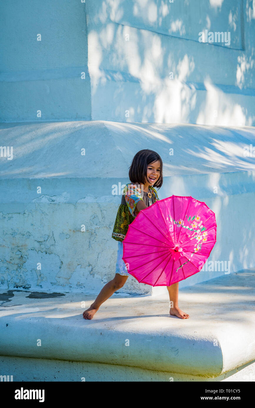 Happy young girl with pink parasol - Stock Image