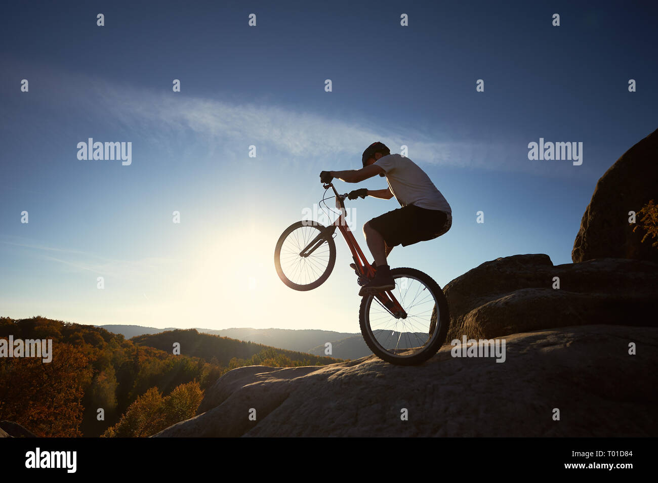Sportsman cyclist standing on back wheel on trial bicycle, man biker balancing on the top of mountain in the summer sunny morning. Blue sky and sunris Stock Photo