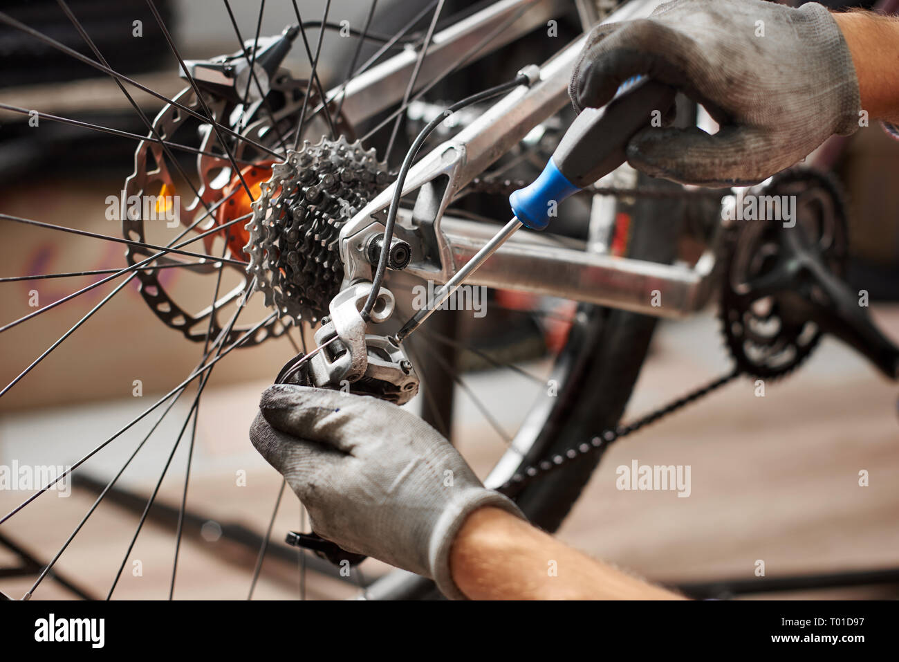 Cropped shot of male mechanic working in bicycle repair shop