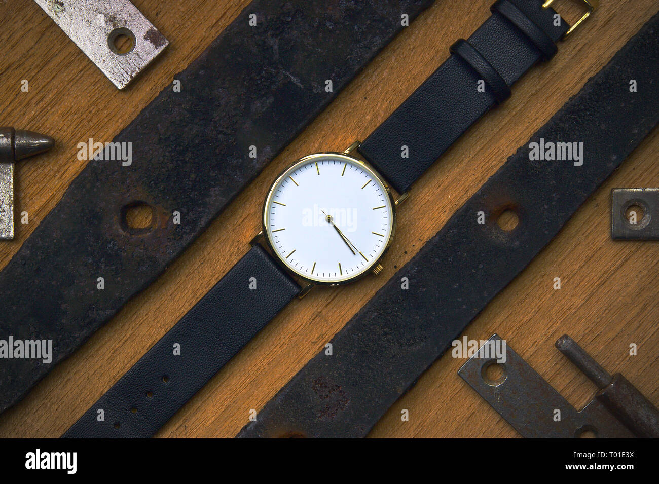 Wristwatch on wooden table from up top. - Stock Image