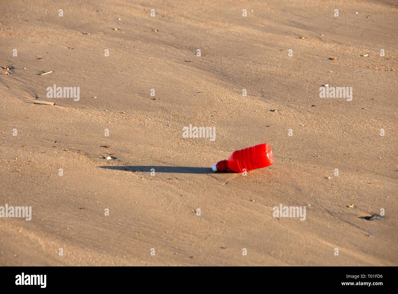 Single red plastic bottle discarded on sandy beach, Hunstanton, Norfolk, England - Stock Image