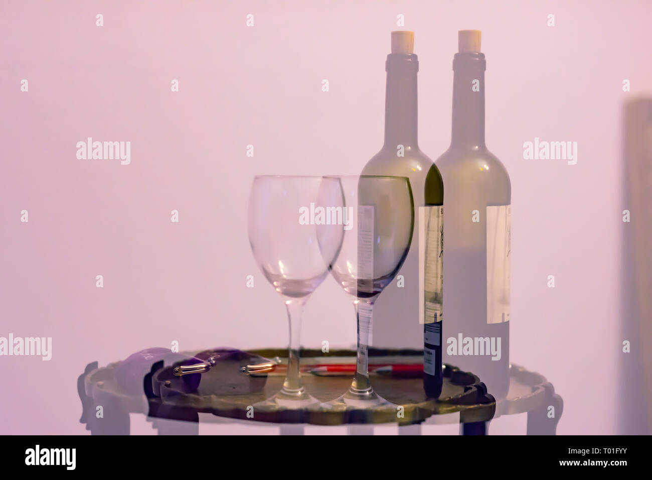 Double vision after alcohol consumption.Double exposure image of bottle of wine and empty glass placed on table with purse. - Stock Image