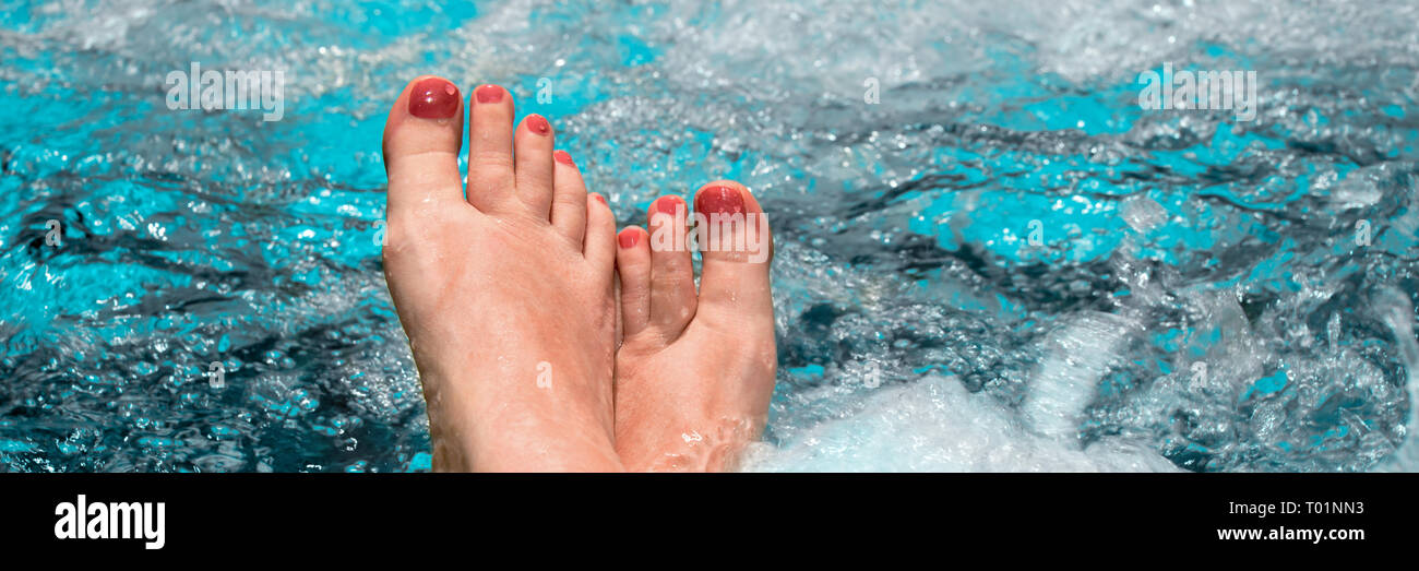 Feet of a woman relaxing in a jacuzzi, panoramic background concept - Stock Image