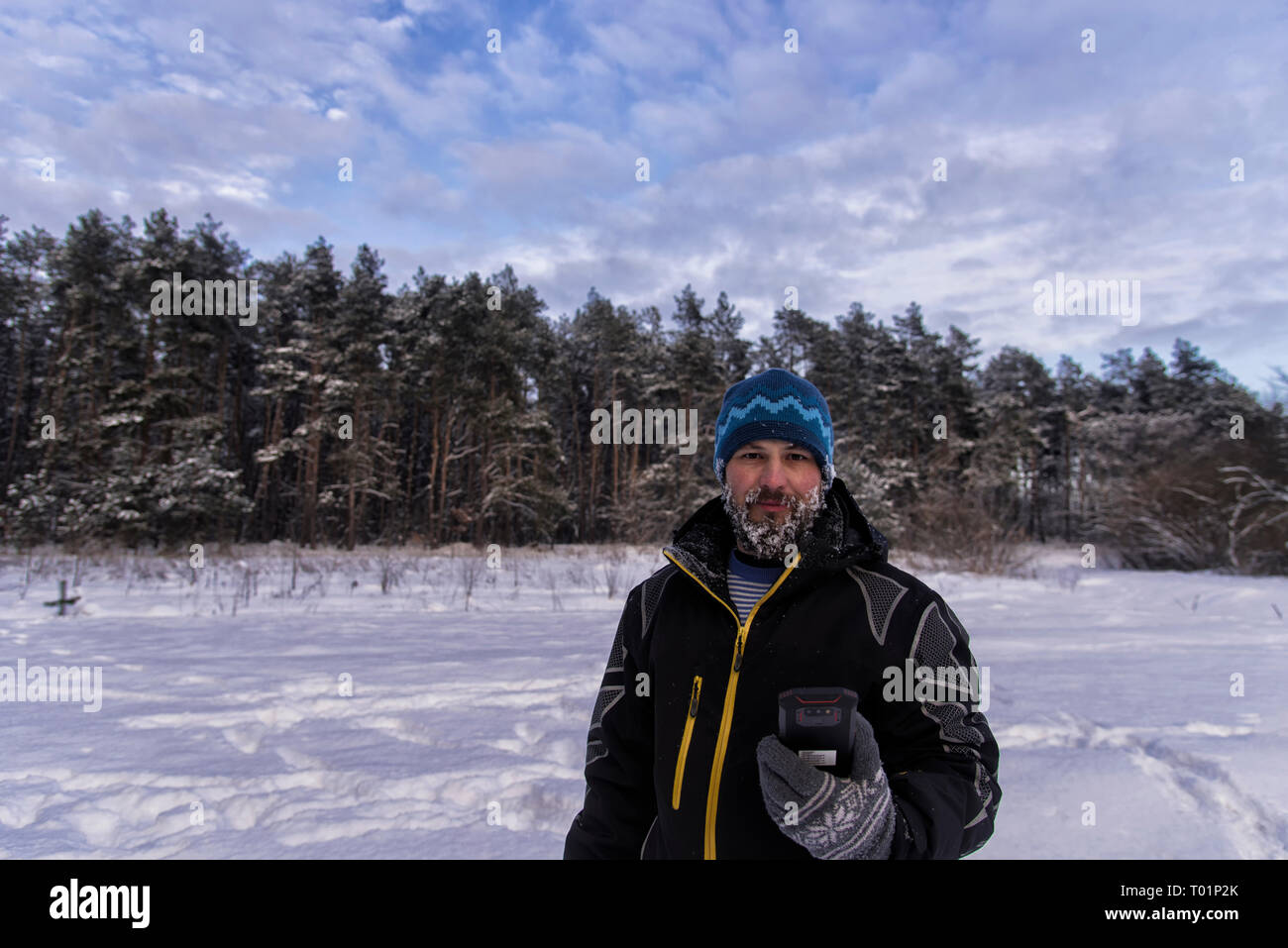 Good-natured bearded man with a snowy beard, slight smile and GPS navigator is standing on the edge of a taiga forest - Stock Image