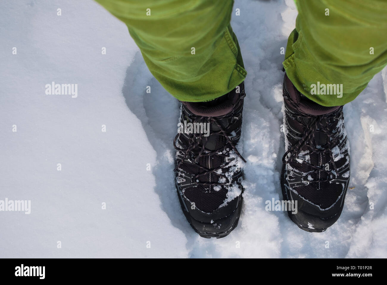 Human feet in hiking boots in the snow - Stock Image