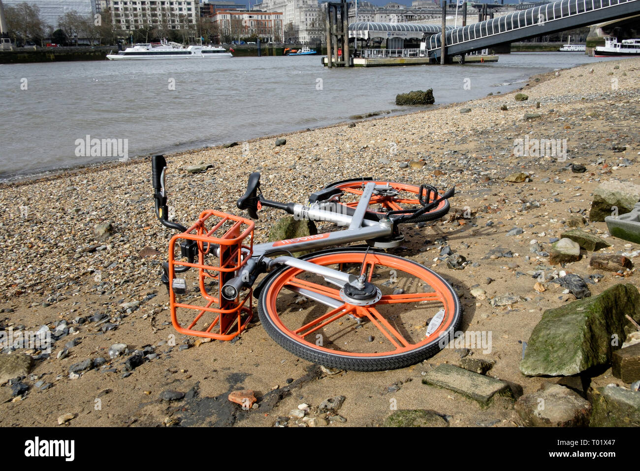 Mobike cycle sharing scheme bike abandoned on foreshore of River Thames, London. - Stock Image