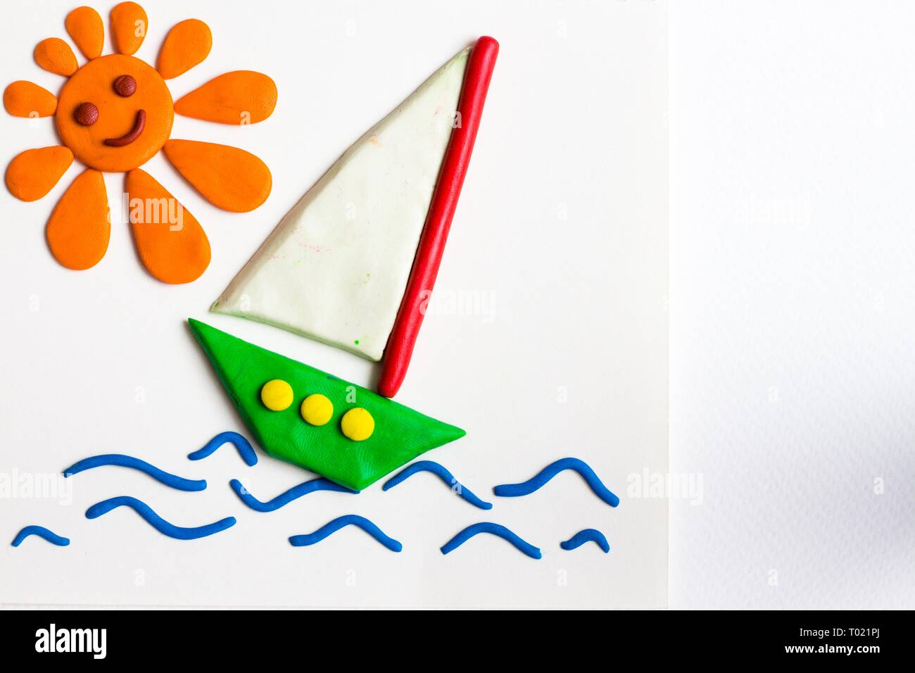 Green ship with a white sail sailing on strong waves. A bright and smiling sun shines above the sea and the ship. - Stock Image