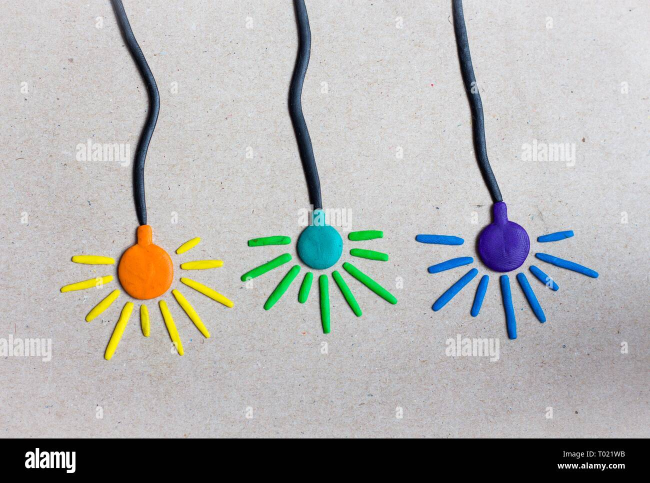 Three colorful lamps of blue, violet and orange colors hang on even wires against a gray wall. Lamps are made of plasticine like the wire and the ligh - Stock Image