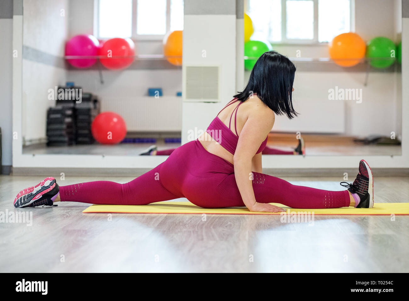 Sports girl sits on the splits in the gym. The concept of sports, a healthy lifestyle, losing weight. - Stock Image