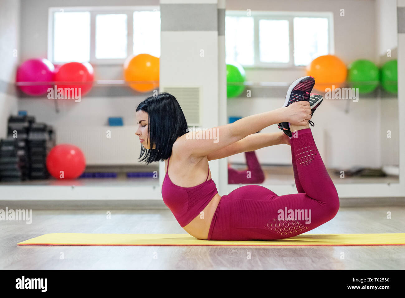 Adult girl is engaged in stretching in the gym. The concept of sports, a healthy lifestyle, losing weight. - Stock Image