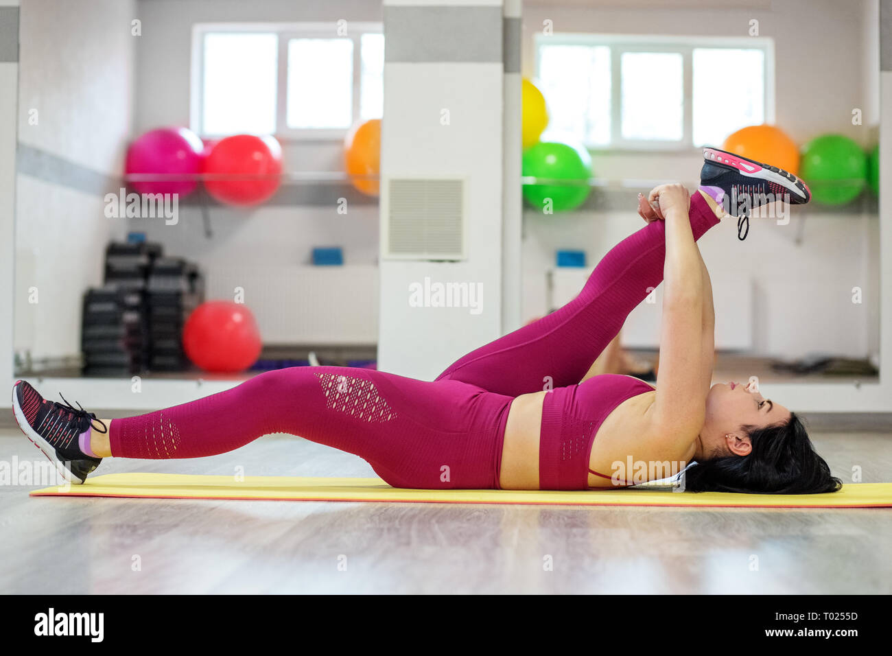 Adult woman is engaged in stretching in the gym. The concept of sports, a healthy lifestyle, losing weight - Stock Image