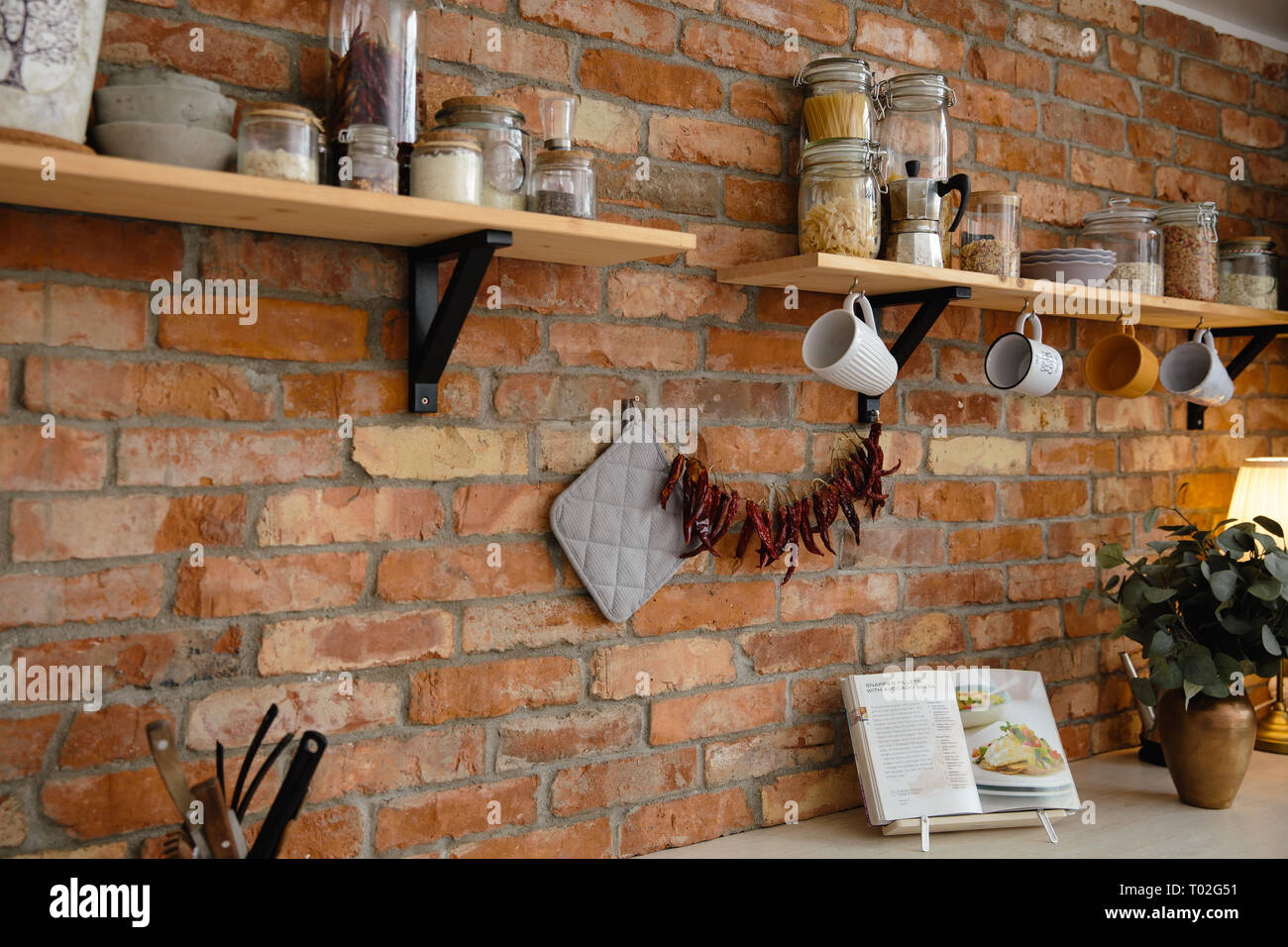 Kitchen loft with designed brick wall and tools hanging on ...