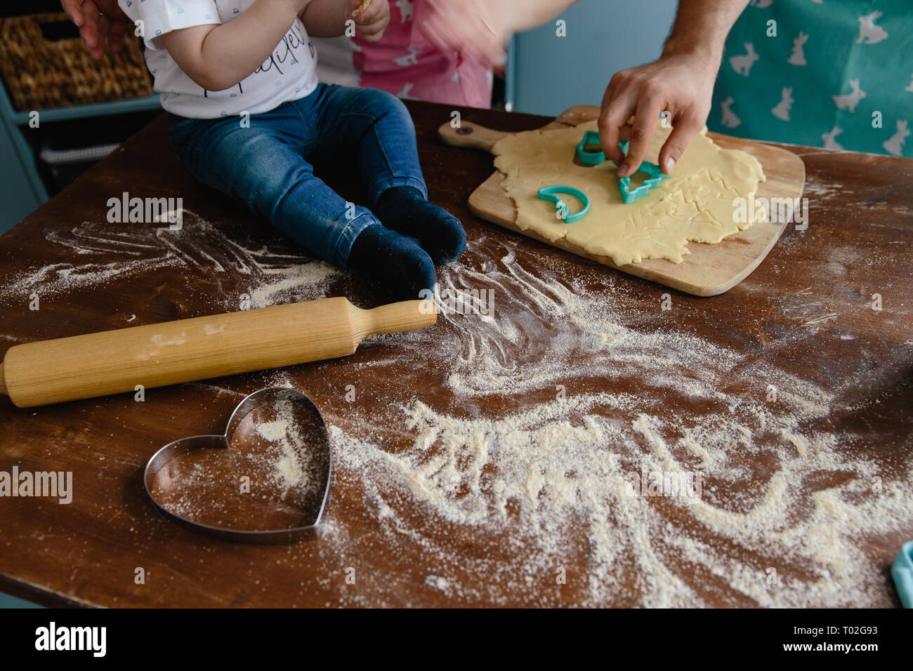 Little boy in jeans mixing flour in the kitchen on a table making some mess - Stock Image