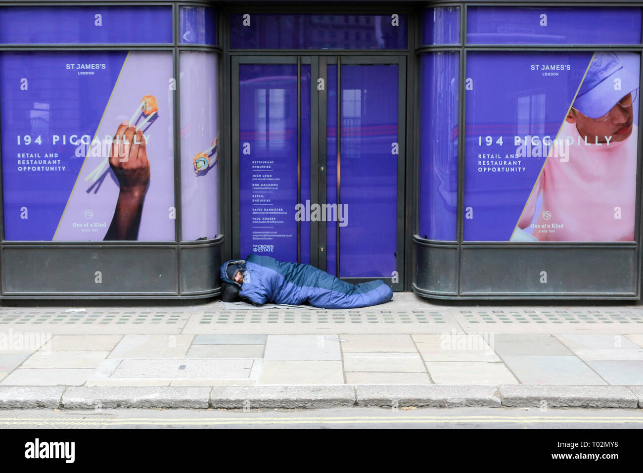 London, UK. 16th March, 2019. A man walks past a homeless man asleep on Piccadilly. Penelope Barritt/Alamy Live news - Stock Image
